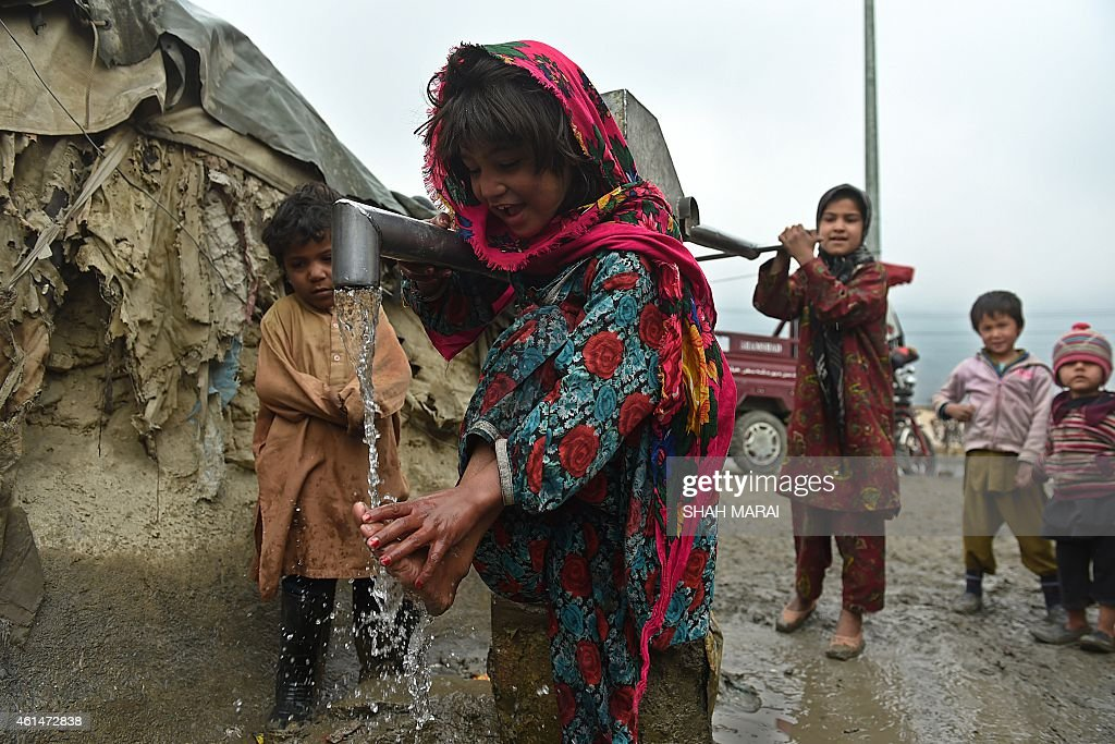 An internally displaced Afghan child washes her feet at a hand pump as she and others wait for their parents to collect food relief aid from the...