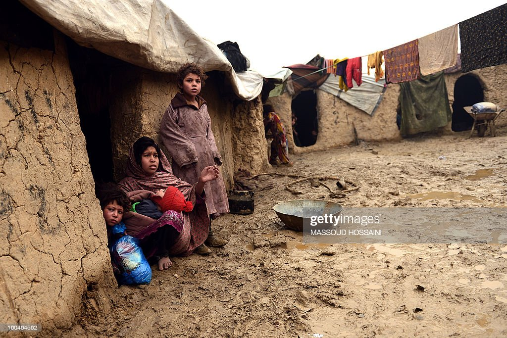 An internally displaced Afghan familt looks on from their hut at Nassaji Camp, east of Kabul, on February 1, 2013. With an ongoing Taliban-led insurgency plaguing the poverty-stricken country, Afghanistan's internally displaced population has reached half a million according to the UN refugee agency, though the actual number is likely to be much higher. AFP PHOTO/Massoud HOSSAINI