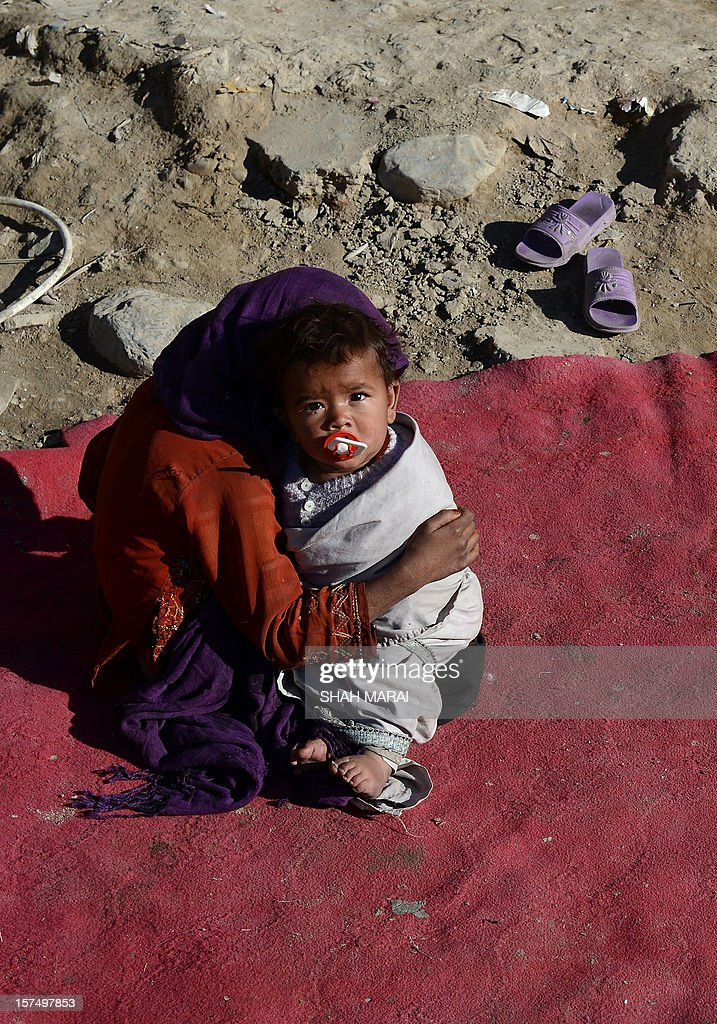 An internally displaced Afghan girl holds her brother as she sits in sunshine outside her mud shelter in a makeshift camp as winter approaches in Kabul on December 4, 2012. The country has nearly half a million displaced people, many living in primitive camps where the cold weather will mean uncertainty for some. AFP PHOTO/SHAH Marai