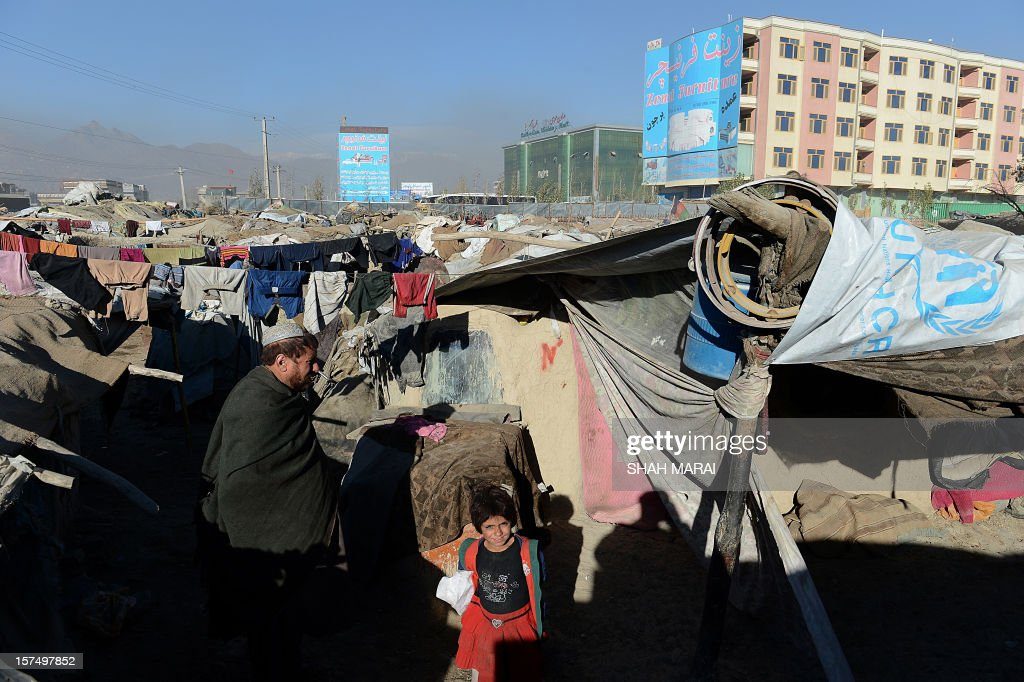 An internally displaced Afghan man and a girl walk outside their mud shelters in a makeshift camp as winter approaches in Kabul on December 4, 2012. The country has nearly half a million displaced people, many living in primitive camps where the cold weather will mean uncertainty for some. AFP PHOTO/SHAH Marai