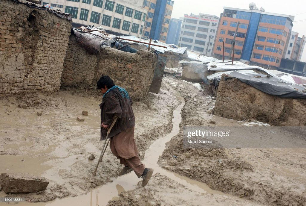 An internally displaced Afghan on crutches makes his way over a rain-filled, muddy ditch at Chamand babrak Camp, on February 3, 2013 in Kabul, Afghanistan. According to the UN refugee agency, Afghanistan's internally displaced population has reached half a million, although the actual figure is believed to be much higher.