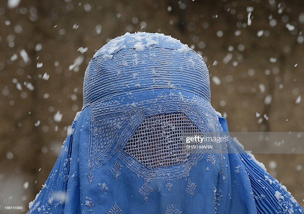 An internally displaced Afghan woman from Helmand province walks to collect winter supplies from the UNHCR at the Charhi Qambar refugee camp on the outskirts of Kabul December 27, 2012. Since the 2001 US-led invasion brought down the Taliban, 3.8 million have returned, leaving 1.6 million behind, most born and brought up in Pakistan. In late October, UNHCR boosted incentives for Afghans to return and around 10,000 Afghans went home from October 23 to November 30 -- more than double the number who were repatriated in the same period last year. AFP PHOTO/ SHAH Marai