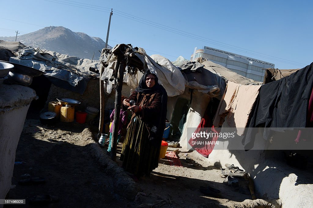 An internally displaced Afghan woman stands outside her mud shelter in a makeshift camp as winter approaches in Kabul on December 4, 2012. The country has nearly half a million displaced people, many living in primitive camps where the cold weather will mean uncertainty for some. AFP PHOTO/SHAH Marai