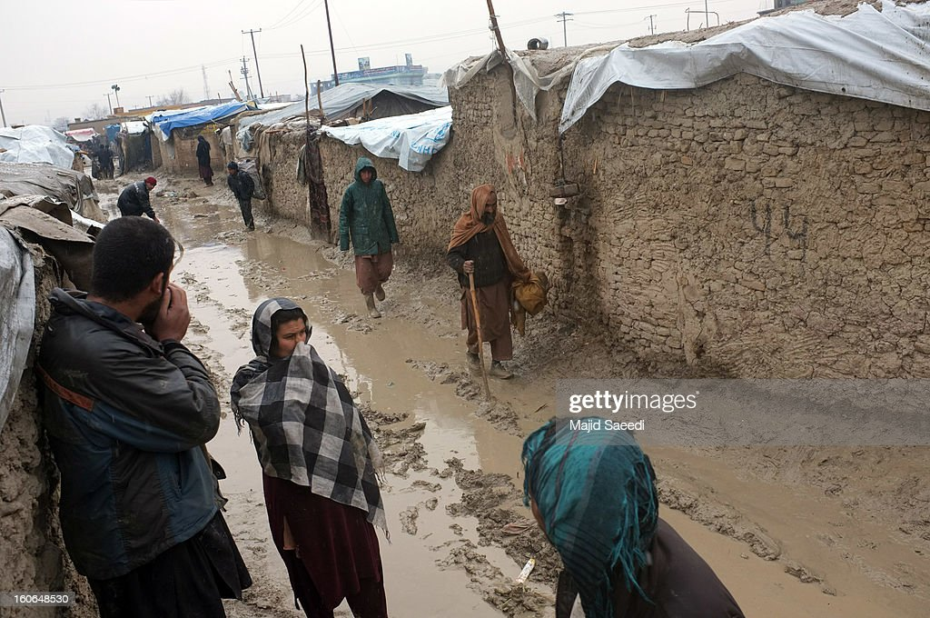 An internally displaced Afghans walk in mud to receive donations from Danish Refugee Council (DRC) at Chamand babrak Camp, on February 3, 2013 in Kabul, Afghanistan. According to the UN refugee agency, Afghanistan's internally displaced population has reached half a million, although the actual figure is believed to be much higher.