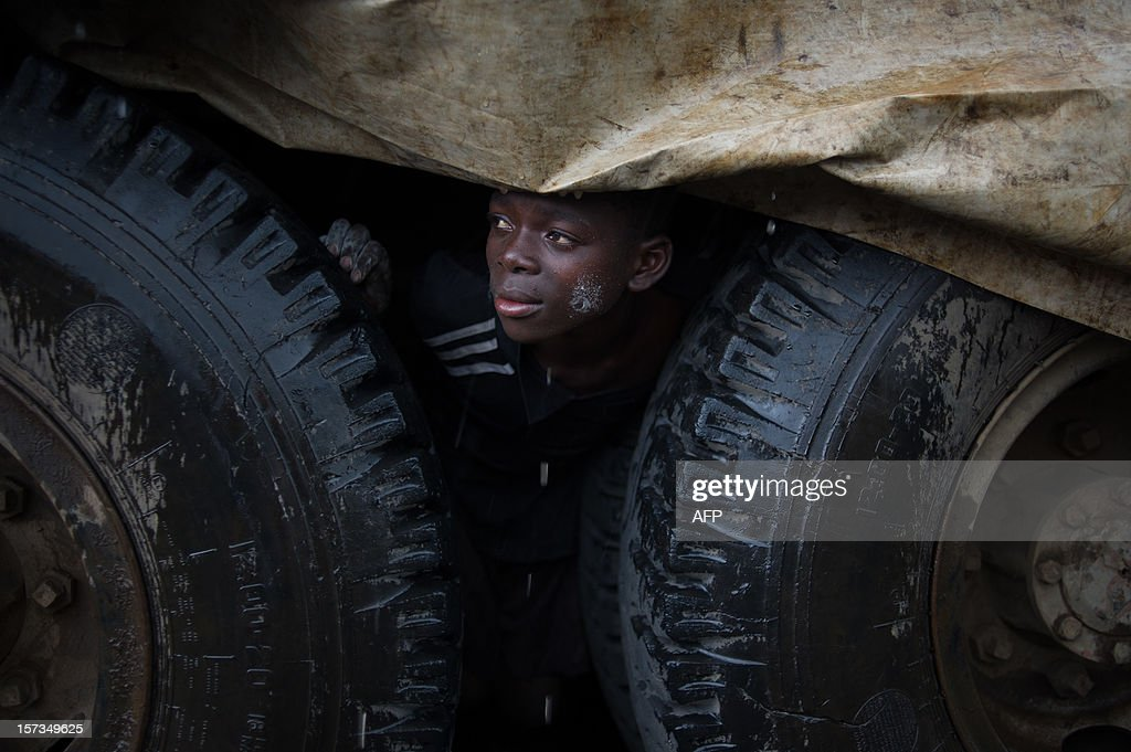 An internally displaced Congolese boy shelters from the rain under a truck in the Mugunga III IDP camp in the east of the Democratic Republic of the Congo on December 2, 2012. UN refugee agency officials reported cases of looting and rape in an attack late yesterday on the giant Mugunga camp, which lies about 10 kilometres (six miles) west of Goma and is home to up to 35,000 displaced people.
