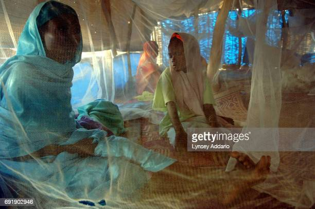 An Internally displaced mother and daughter sit beneath a mosquito net while being treated for malnutrition at the Kalma camp for IDPs in Nyala South...