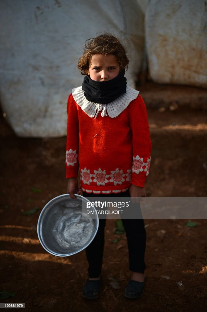 An internally displaced Syrian girl holds an empty pot in the Maiber al-Salam refugee camp along the Turkish border in the northern province of Aleppo on April 17, 2013. UN agencies helping to care for the millions driven from their homes in Syria by two years of conflict warned on Tuesday that they face 'impossible' choices as funding fails to meet soaring needs. In all, some 1.3 million people have now fled Syria and some 200,000 more are crossing into neighbouring countries each month.