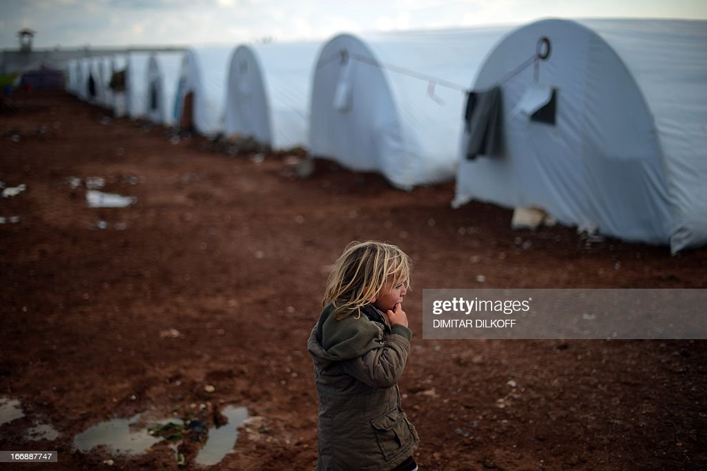 An internally displaced Syrian girl stands near tents in the Maiber al-Salam refugee camp along the Turkish border in the northern province of Aleppo on April 17, 2013. UN agencies helping to care for the millions driven from their homes in Syria by two years of conflict warned that they face 'impossible' choices as funding fails to meet soaring needs. In all, some 1.3 million people have now fled Syria and some 200,000 more are crossing into neighbouring countries each month.