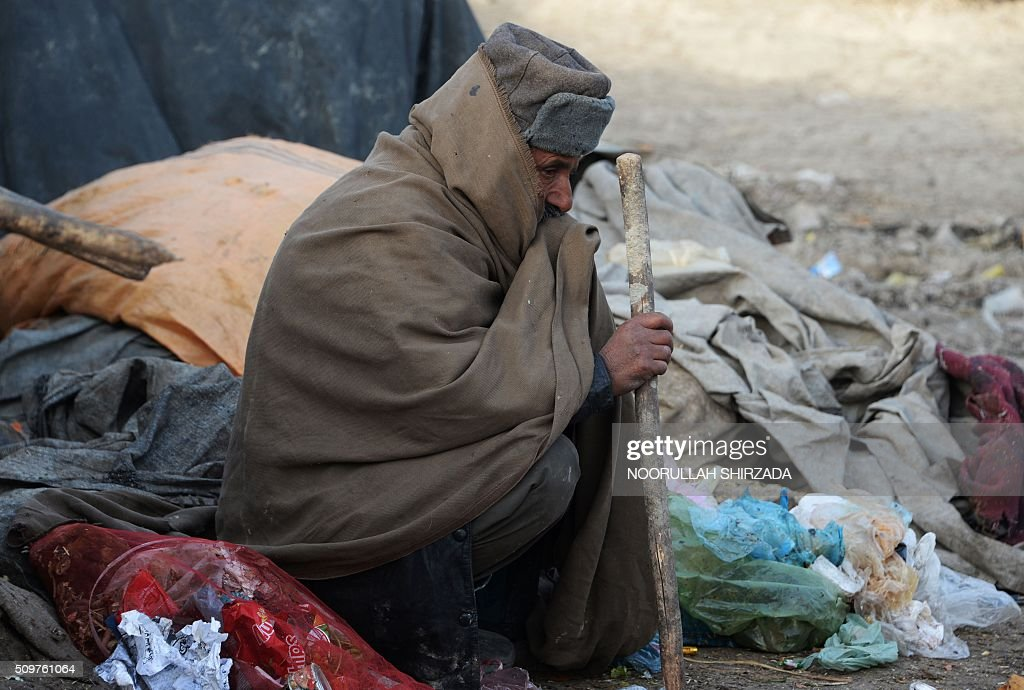 An internally-displaced Afghan man sits outside his temporary home on the outskirts of Kabul on February 12, 2016. As winter continues across Central Asia, many Afghans struggle to provide adequate food and shelter for their families. AFP PHOTO / Noorullah Shirzada / AFP / Noorullah Shirzada