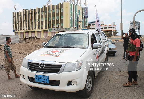 An International Committee of the Red Cross vehicle drives past Yemeni fighters loyal to President Abedrabbo Mansour Hadi on April 15 in the southern...