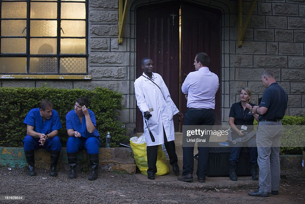 An International forensic team talk to a local Pathologist outside the city mortuary on September 26, 2013 in Nairobi, Kenya. The country is observing three days of national mourning as security forces begin the task of clearing and securing the Westgate shopping mall following a four-day siege by militants.