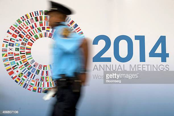 An International Monetary Fund police officer walks past a sign for the IMF and World Bank Group Annual Meetings in Washington DC US on Tuesday Oct 7...