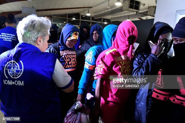 An International Organization for Migration member stand next to Ivorian migrants returning from Libya to be repatriated in their country as they...