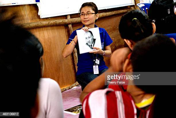 An International Organization for Migration staff member shows pictures of American culture icons to a group of young Burmese refugees during a...
