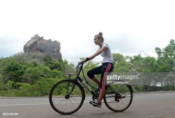 An international tourist rides a bicycle near Sigiriya Rock in Sigiriya northcentral Sri Lanka on August 19 2017 The Sigiriya rock 160 kilometres...