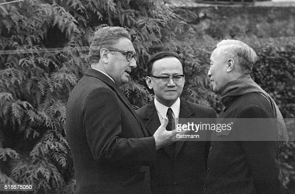 An interpreter stands between White House Advisor Henry Kissinger and Hanoi's senior representative Le Duc Tho as they converse in the garden of a...