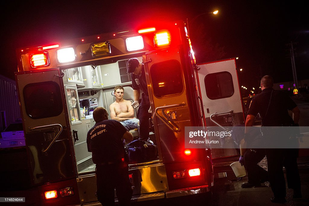 An intoxicated man sits inside an ambulance outside a bar on July 26, 2013 in Williston, North Dakota. The state has seen a rise in crime, automobile accidents and drug usage recently, due in part to the oil boom which has brought tens of thousands of jobs to the region, lowering state unemployment and bringing a surplus to the state budget.
