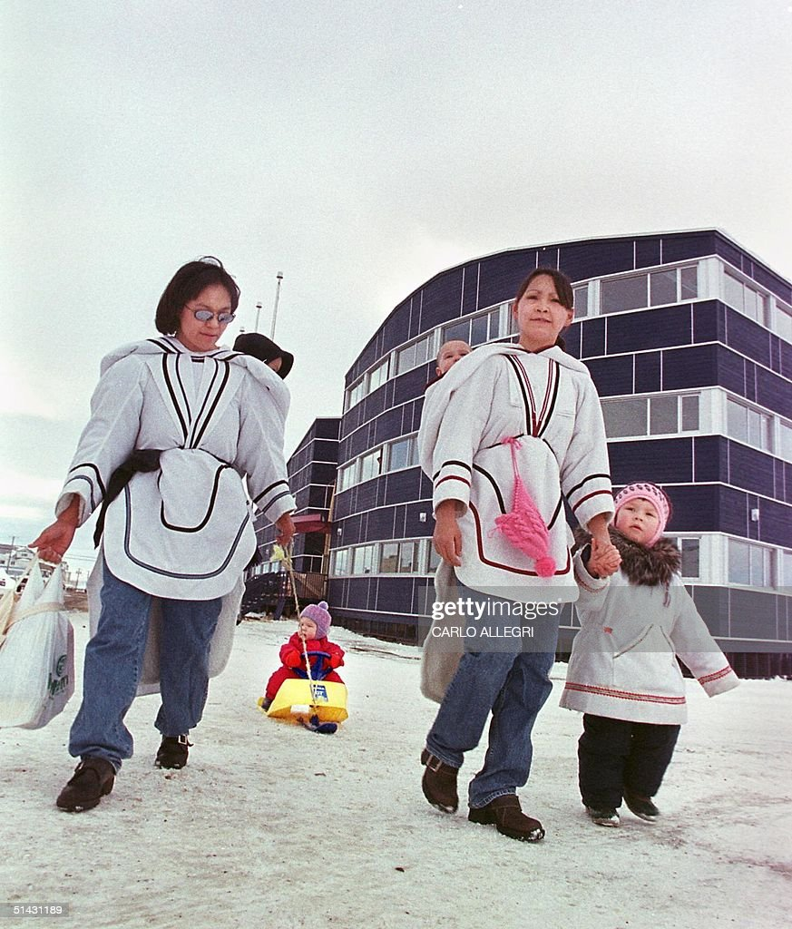 an inuit family walsk past the new legislature bui pictures