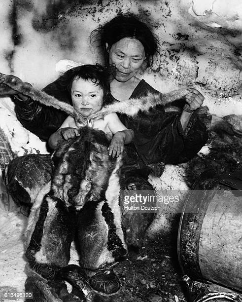 An Inuit mother dresses her young child in a fur snowsuit