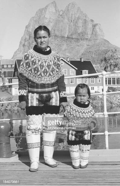 An Inuit woman and a girl posing with their traditional costumes Behind them some houses of a Danish village in Greenland May 1962