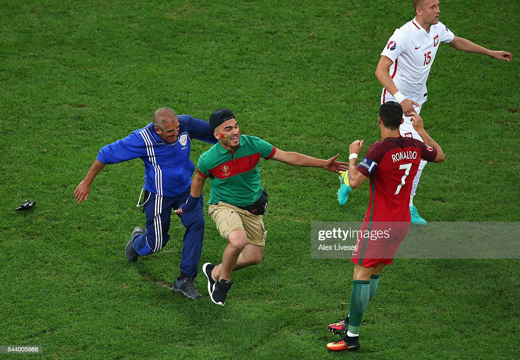 An invading fan tries to hug <a gi-track='captionPersonalityLinkClicked' href=/galleries/search?phrase=Cristiano+Ronaldo+-+Soccer+Player&family=editorial&specificpeople=162689 ng-click='$event.stopPropagation()'>Cristiano Ronaldo</a> of Portugal during the UEFA EURO 2016 quarter final match between Poland and Portugal at Stade Velodrome on June 30, 2016 in Marseille, France.
