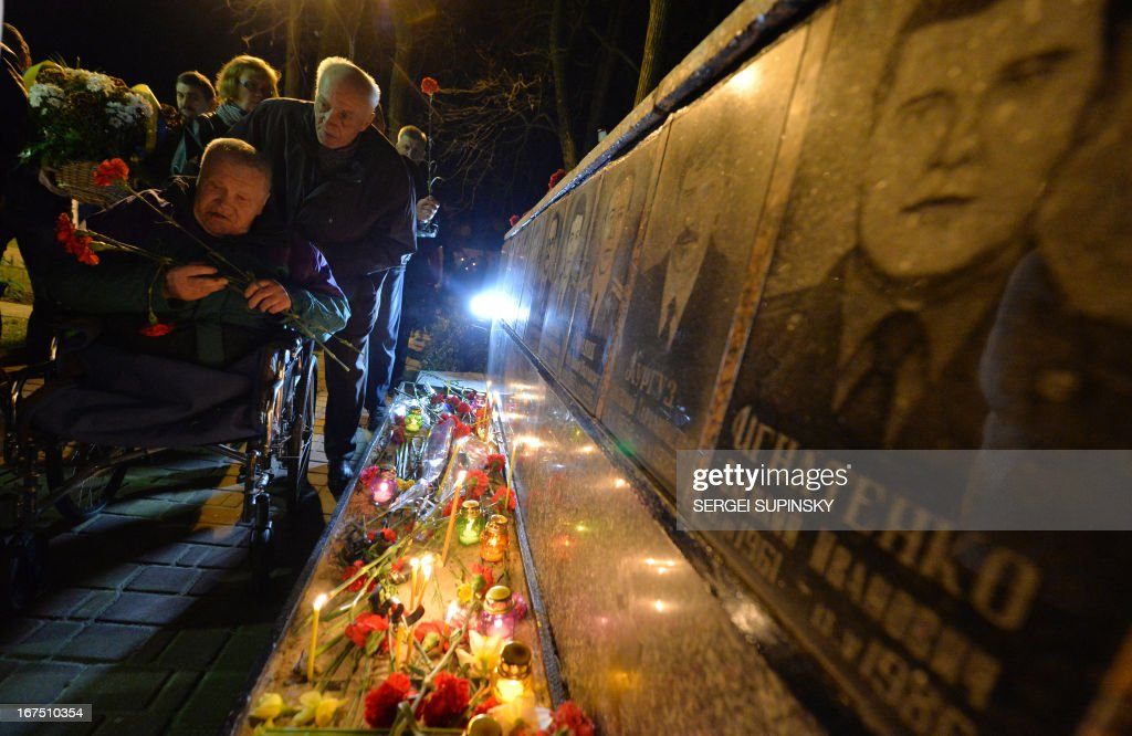 An invalid lays flowers to portraits at the monument to Chernobyl victims in Slavutich, some 50 kilometres (30 miles) from the accident site, and where many of the power station's personnel used to live, during a memorial ceremony early on April 26, 2013. Ukraine on April 26 marks the 27th anniversary of the Chernobyl disaster which was the world's worst nuclear accident.