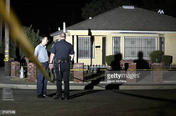 An investigator and a police officer talk near the house where five people including three children were murdered on July 8 2003 in Bakersfield...