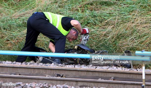 An investigator examines part of the car which collided with a train killing the motorist late Monday evening on the East Coast Main Line in the...