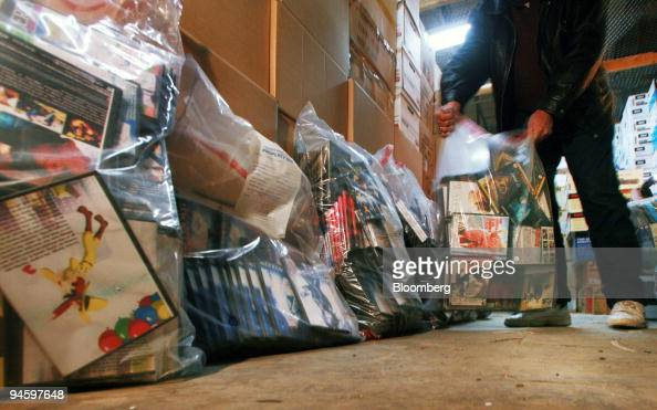 An investigator for the Canadian Motion Picture Distributors AntiPiracy Operation loads evidence bags of illegally copied movies into an evidence...