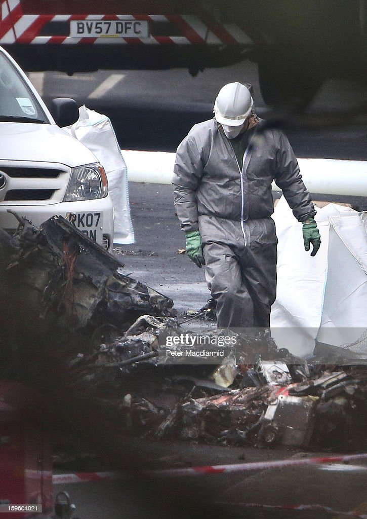 An investigator holds a piece helicopter wreckage as he stands in its mangled remains on January 17, 2013 in London, England. Police cordons have remained in place as investigations continue into the cause of yesterday's helicopter crash in which two people died.