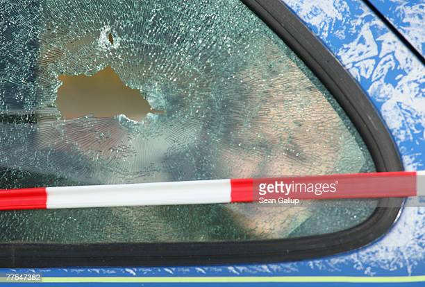 An investigator peers through the shattered window of a car struck by a bullet outside a branch of Postbank bank after an attempted robbery that left...