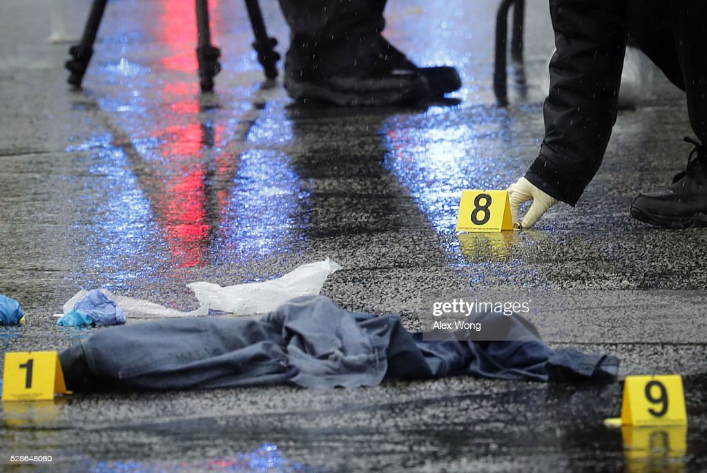 An investigator picks up a shell casing that was left behind at a shooting crime scene at Westfield Montgomery Mall May 6, 2016 in Bethesda, Maryland. At least two people were killed and two injured in two separate shootings in Montgomery County, Maryland.