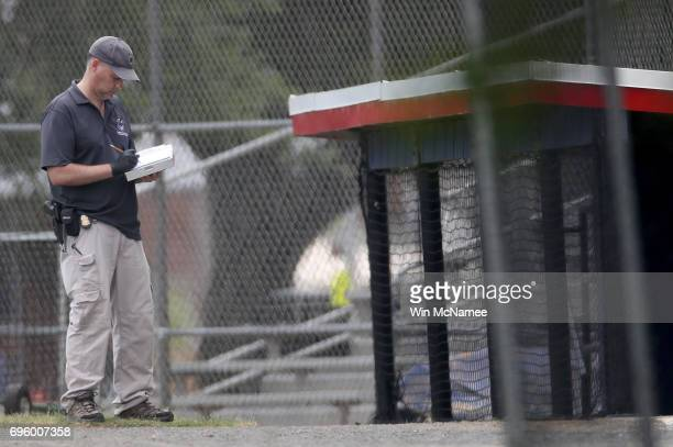 An investigator takes notes next to the third base dugout of the Eugene Simpson Field the site where a gunman opened fire June 14 2017 in Alexandria...