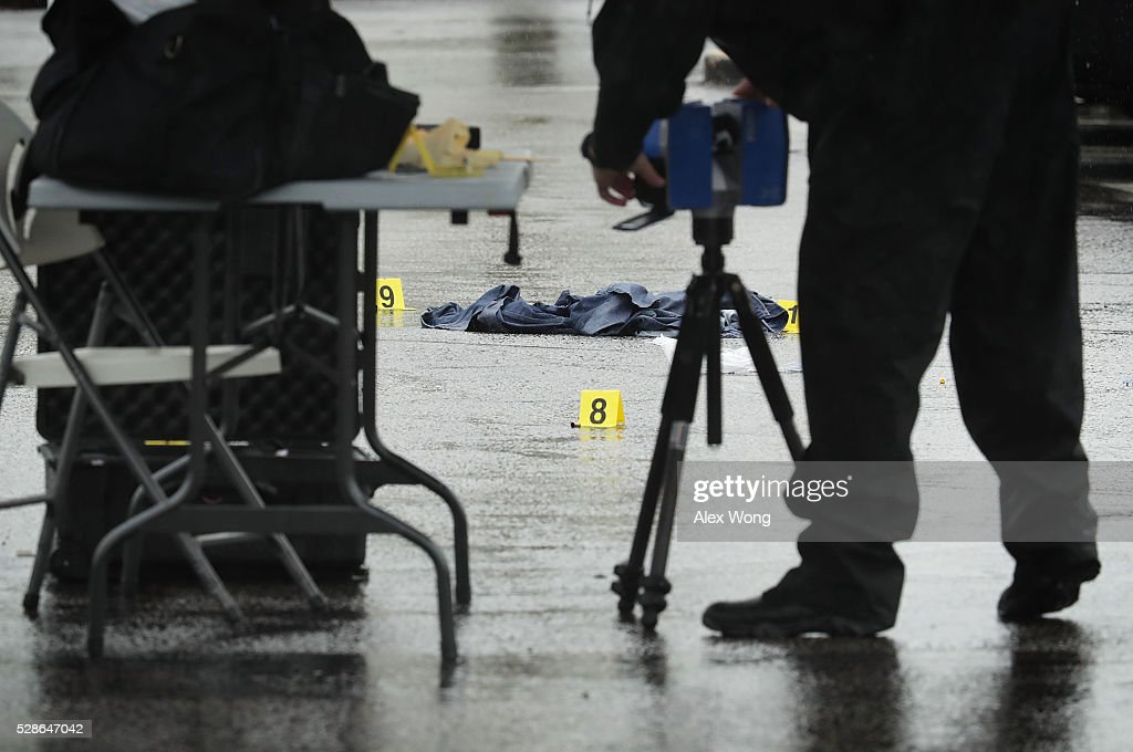 An investigators scans a shooting crime scene with a device at Westfield Montgomery Mall May 6, 2016 in Bethesda, Maryland. At least two people were killed and two injured in two separate shootings in Montgomery County, Maryland.
