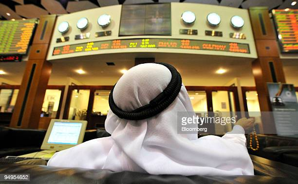 An investor checks the stock markets while on the floor at the Dubai Financial Market at the Dubai World Trade Centre in Dubai United Arab Emirates...