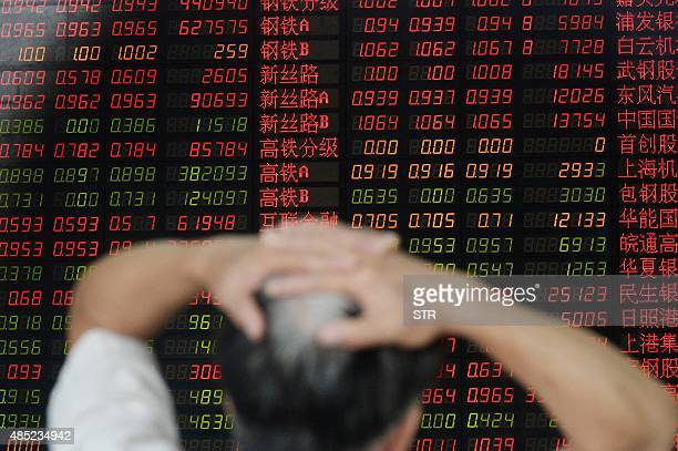 An investor gestures as he checks share prices at a securities firm in Shanghai on August 26 2015 Shanghai stocks closed down 127 percent in volatile...