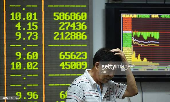An investor gestures in front of screens showing share prices at a securities firm in Hangzhou in eastern China's Zhejiang province on August 24 2015...