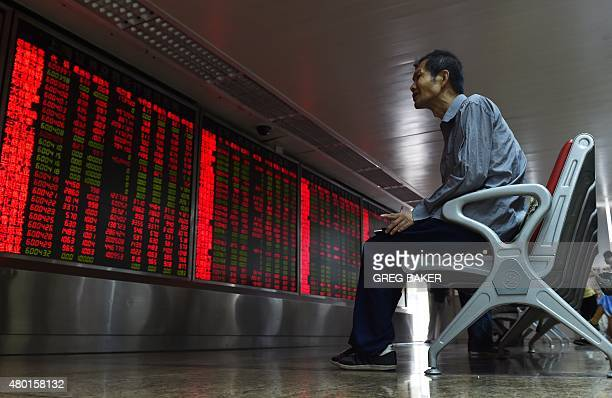 An investor looks at a board showing stock market movements at a securities company in Beijing on July 10 2015 Chinese stocks surged for a second day...