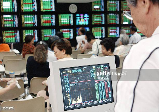 An investor looks at a monitor showing the stock index at a local securities in Taipei 29 July 2003 Taiwan share prices fell 201 percent Tuesday in...