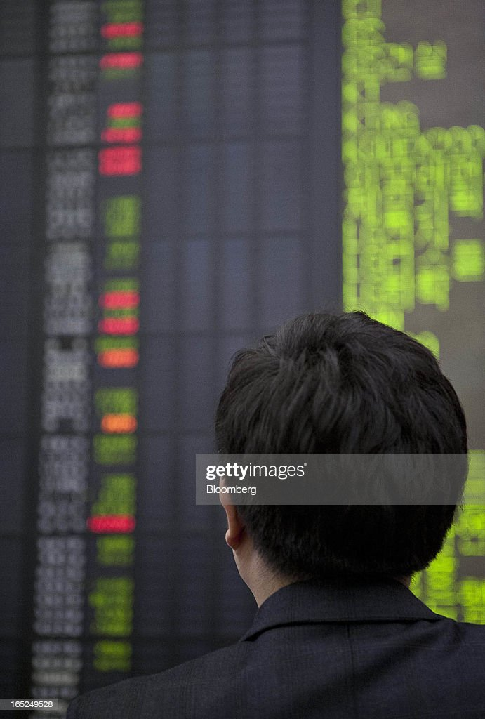 An investor looks at a stock board at a Daishin Securities Co. branch in Seoul, South Korea, on Tuesday, April 2, 2013. International investors sold the most South Korean equities in 10 months in March amid concerns the nation's exporters will lose market share to Japanese rivals and as tension with North Korea rose. Photographer: Jean Chung/Bloomberg via Getty Images
