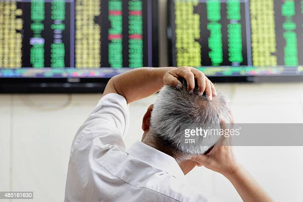 An investor looks at screens showing share prices at a securities firm in Qingdao in eastern China's Shandong province on August 25 2015 Shanghai...