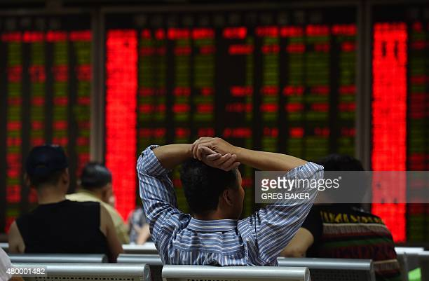 An investor looks at screens showing stock market movements at a securities company in Beijing on July 9 2015 China's market regulator has barred...