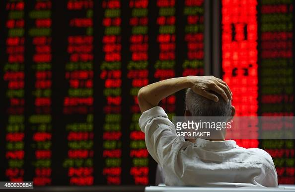 An investor looks at screens showing stock market movements at a securities company in Beijing on July 14 2015 Hundreds of firms were expected to...