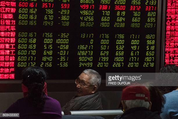 An investor looks at screens showing stock market movements at a securities company in Beijing on January 5 2016 Volatility shook Chinese stock...