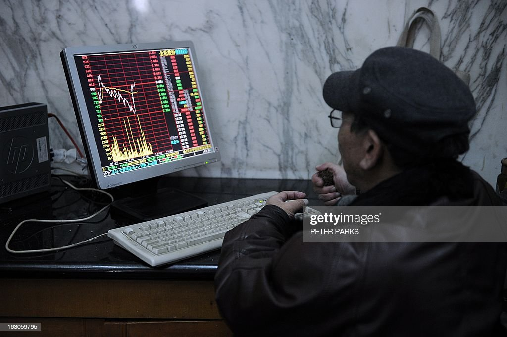 An investor looks at stock prices on a screen at a securities exchange in Shanghai on March 4, 2013. Chinese shares were down 3.05 percent in early afternoon trade as property stocks were hit by government measures announced last week to control housing prices, dealers said. AFP PHOTO/Peter PARKS