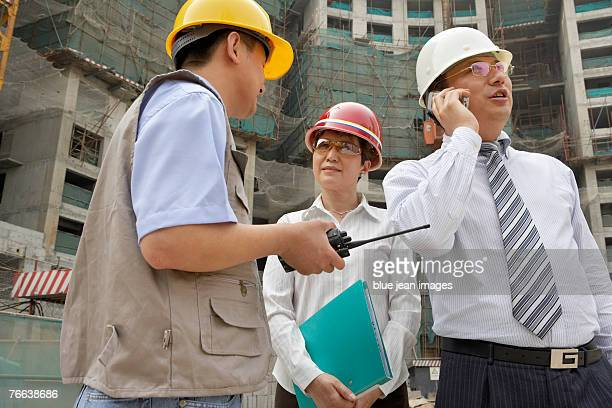 An investor makes a call while an engineer discusses the construction project.