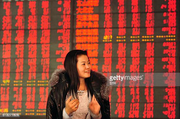 An investor makes her way in front of a screen showing stock market movements in a securities firm in Fuyang east China's Anhui province on March 2...