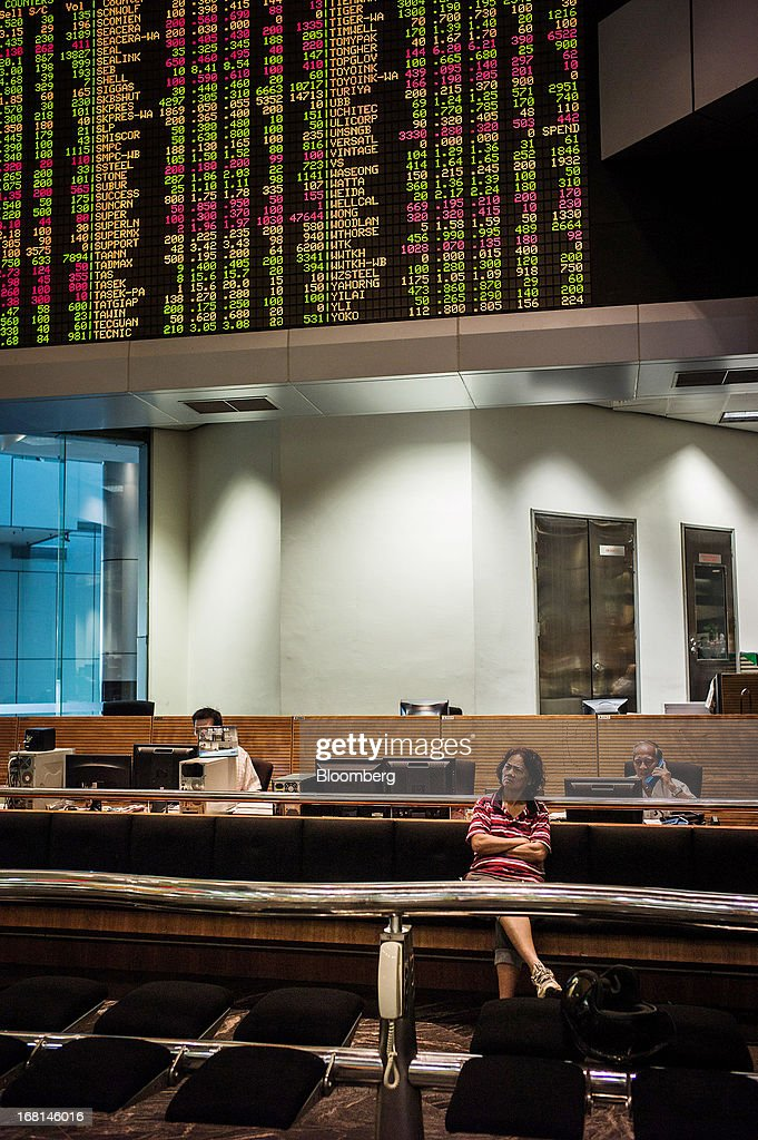 An investor monitors stock prices as traders work at their desks in the trading gallery at the RHB Investment Bank Bhd. headquarters in Kuala Lumpur, Malaysia, on Monday, May 6, 2013. The biggest surge in Malaysian stocks since 2008 has turned into a money-losing day for investors who piled in at the height of the rally sparked by Prime Minister Najib Razak's election victory. Photographer: Sanjit Das/Bloomberg via Getty Images