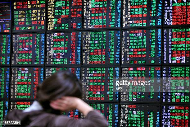An investor monitors the stock market at a securities brokerage in Taipei on April 16 2013 Asian shares were mixed on April 16 with earlier losses...