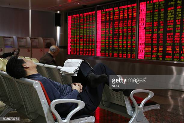 An investor naps while observing stock market at an exchange hall on January 8 2016 in Beijing China Chinese stock market experienced a halt on...